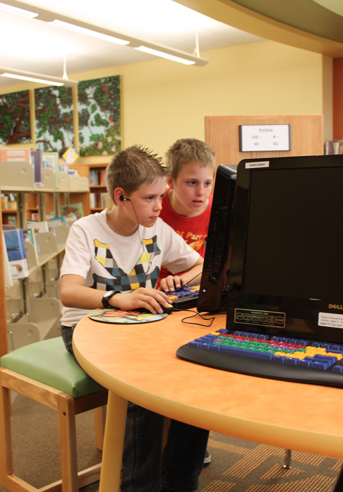 Two tween boys playing on desktop computer in library